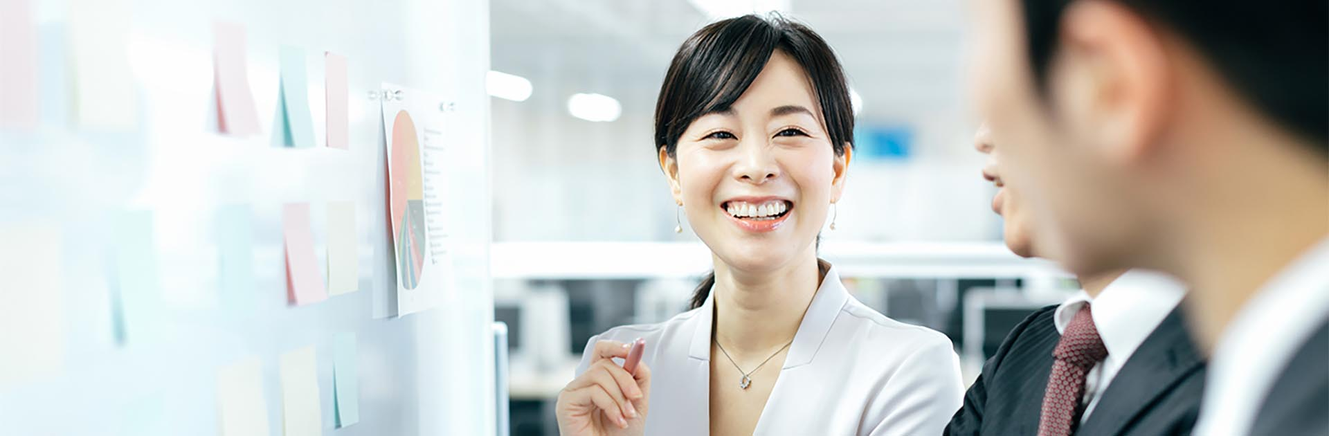 Japanese business woman smiling with her co workers