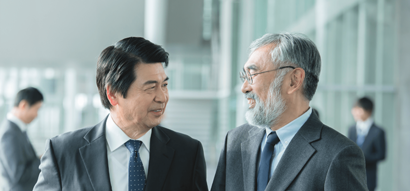 Two Japanese businessmen smiling while standing